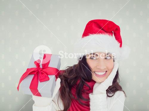 Composite image of surprised brunette in santa hat holding gift