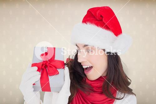 Composite image of astonished brunette in santa hat showing gift