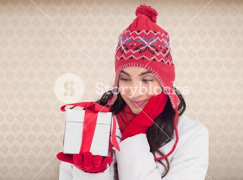 Composite image of content brunette in winter clothes holding gift