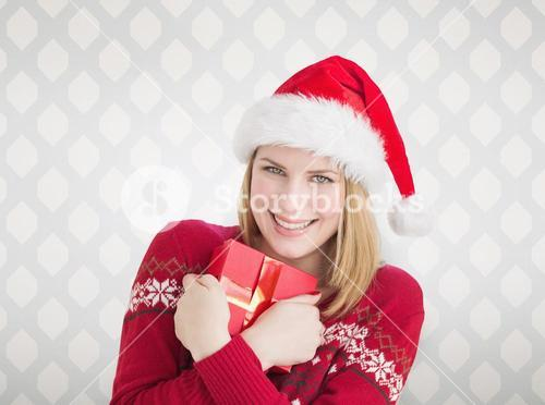 Composite image of woman holding christmas present