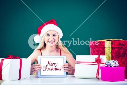 Composite image of festive blonde shopping online with tablet pc