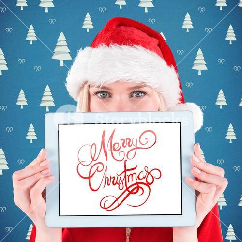 Composite image of festive blonde holding a tablet pc