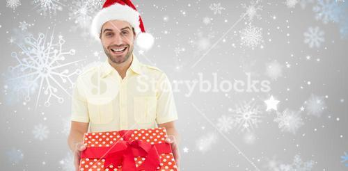 Composite image of smiling man wearing santa hat while holding gift