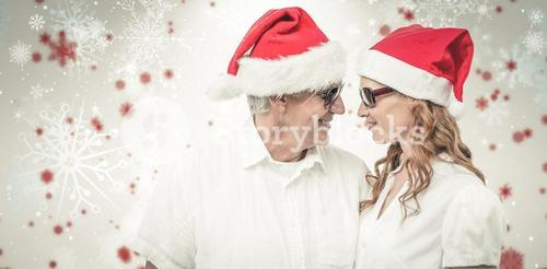 Composite image of festive couple smiling at each other