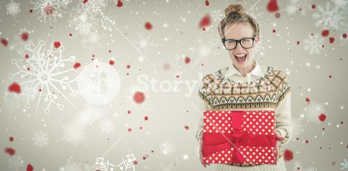 Composite image of excited geeky hipster holding present