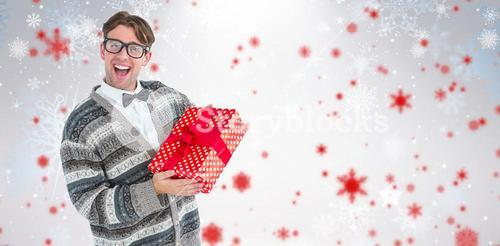 Composite image of happy geeky hipster with wool jacket holding present