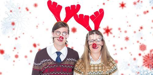 Composite image of portrait of smiling man and woman wearing red reindeer horn