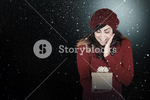 Composite image of surprised brunette holding a gift