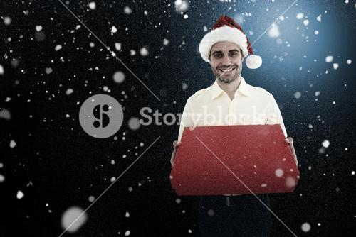 Composite image of happy man wearing santa hat while holding red gift