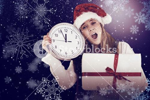 Composite image of festive blonde showing a clock and gift