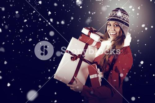 Composite image of pretty redhead in warm clothing holding gifts