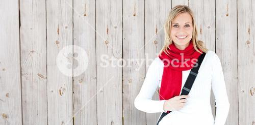 Composite image of portrait of a delighted student with scarf smiling at the camera
