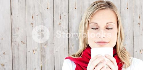 Composite image of portrait of a young woman enjoying her hot coffee in the winter