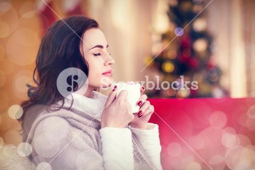 Composite image of brunette enjoying a hot chocolate at christmas
