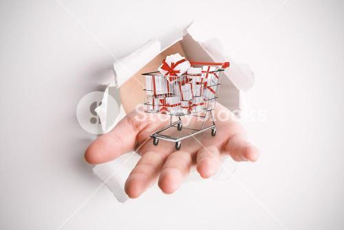 Composite image of hand bursting through paper