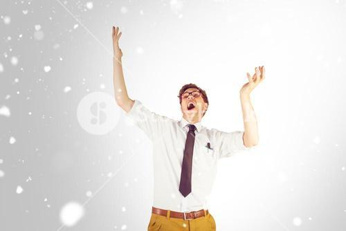 Composite image of geeky businessman standing with arms raised