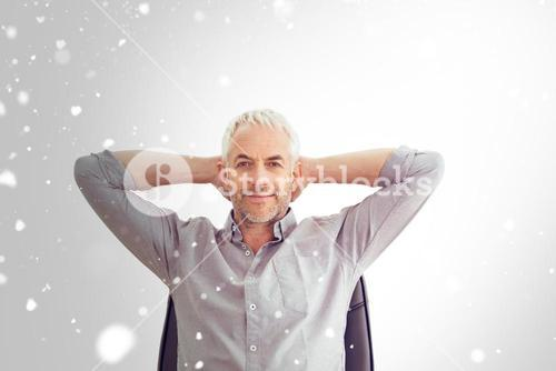 Composite image of relaxed mature businessman with hands behind head
