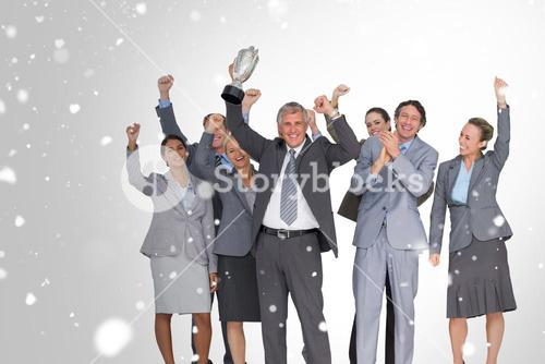 Composite image of excited business team cheering at camera with trophy