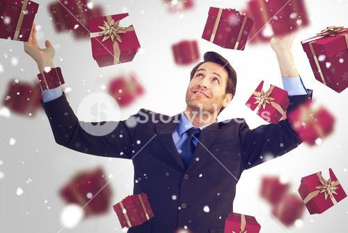 Composite image of businessman cheering with hands raised