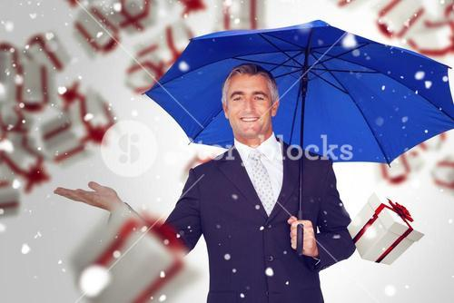 Composite image of smiling businessman holding blue umbrella with hand out