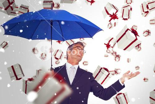 Composite image of businessman holding blue umbrella with hand out