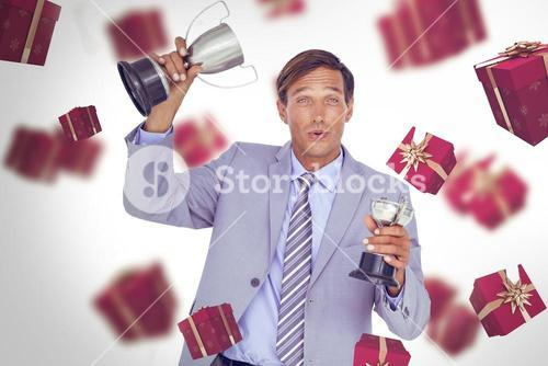 Composite image of portrait of successful businessman holding trophies