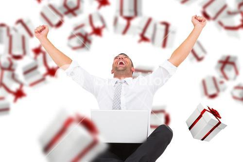 Composite image of businessman using laptop and cheering