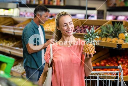 Smiling woman holding and looking a pineapple