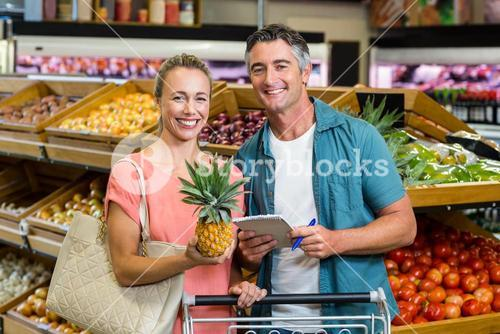 Smiling couple holding a pineapple and a grocery list