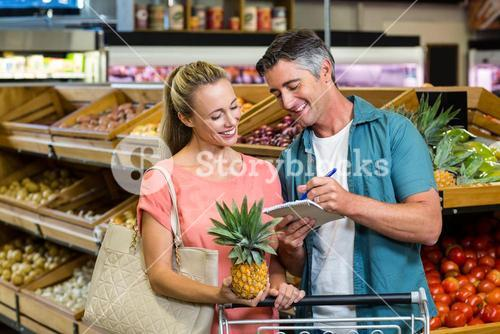 Smiling couple looking at the grocery list