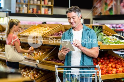 Smiling man looking at the grocery list