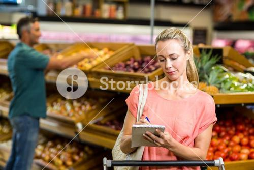 Pretty woman checking grocery list