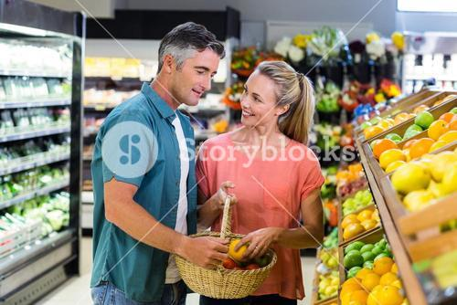 Happy couple putting apple in the basket