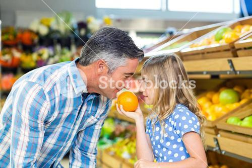 Cute girl holding an orange to her father