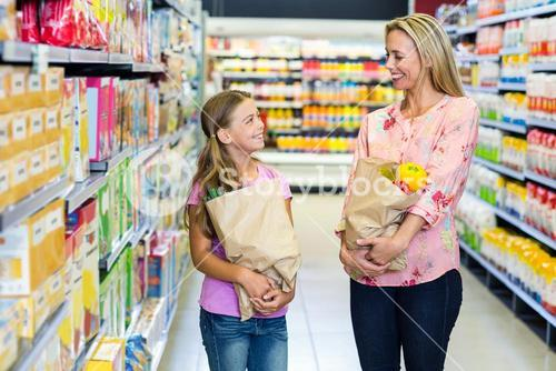 Smiling mother and daughter with grocery bags