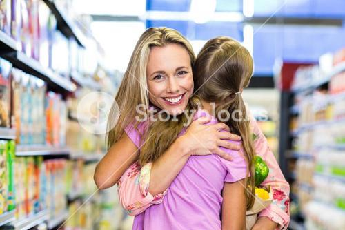 Smiling mother and daughter with grocery bag hugging