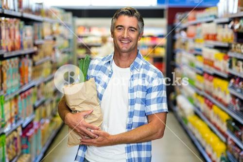 Smiling man holding grocery bag
