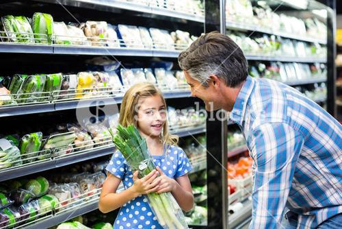 Father and daughter buying celery