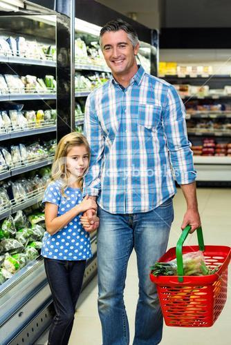 Smiling father and daughter at the supermarket