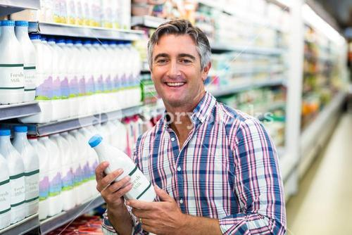Smiling man holding milk bottle