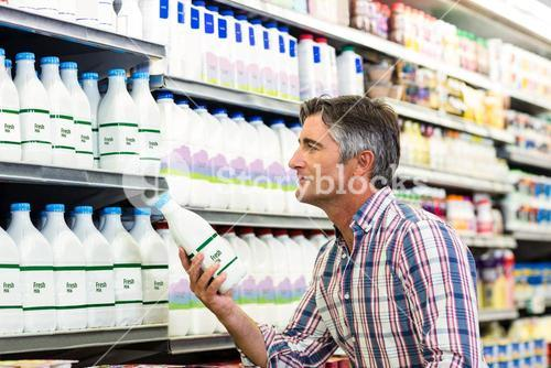 Handsome man buying milk