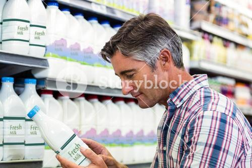 Handsome man in the supermarket looking at milk bottle