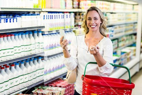 Smiling woman holding smartphone and shopping basket
