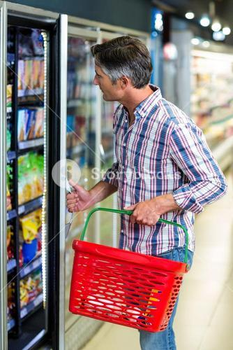 Man opening supermarket fridge