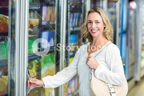 Smiling woman opening supermarket fridge