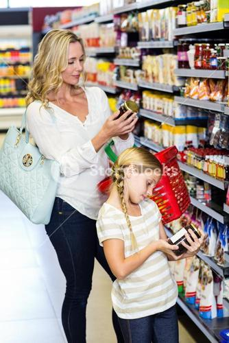 Mother and daughter reading nutritional values of products
