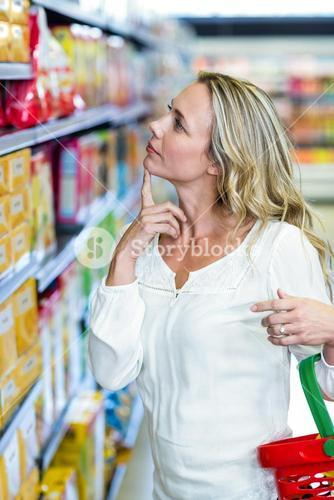 Thoughtful woman looking at shelves