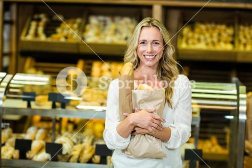 Beautiful woman holding paper bag with bread