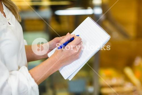 Woman checking list at supermarket