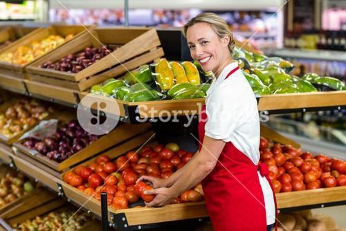 Portrait of smiling seller holding tomatoes